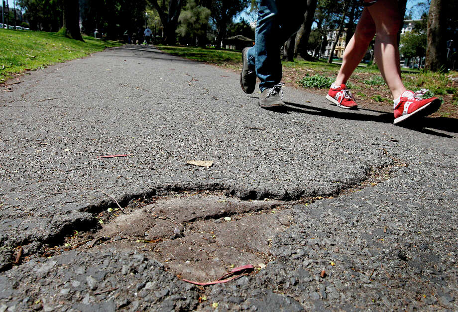 Joggers and walkers veer away from areas where the old asphalt has worn away Monday April 8, 2013. The southern walkway along the Panhandle at the east end of San Francisco\'s Golden Gate Park is in need of resurfacing. Photo: Brant Ward, The Chronicle / ONLINE_YES