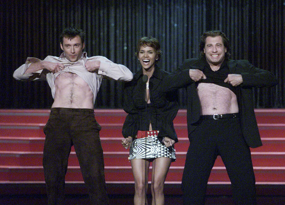 Hugh Jackman and John Travolta pull up their shirts after Halle Berry encouraged them to show a piece of anatomy at the 2001 MTV Movie Awards at the Shrine Auditorium in Los Angeles Saturday, June 2, 2001. Photo: Kevin Winter, Getty Images / Getty Images North America