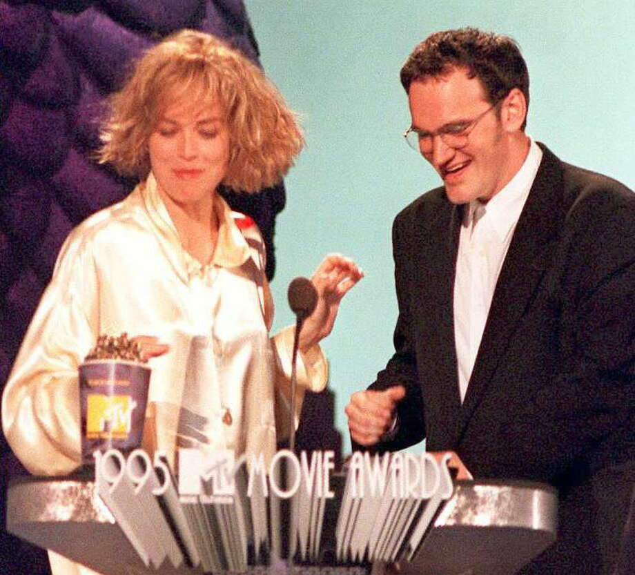 "Actress Sharon Stone (L) presents director Quentin Tarintino with the award for best movie, ""Pulp Fiction,"" during taping of the 1995 MTV Movie Awards 10 June in Burbank, California. Photo: Vince Bucci, AFP/Getty Images / AFP"