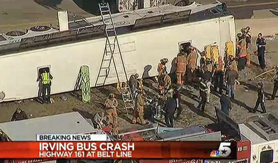 This frame grab provided by KXAS-TV shows emergency personnel at the scene where a chartered bus overturned on a highway near Dallas-Fort Worth International Airport in Irving, Texas.  Authorities say at least six people are hospitalized.   MANDATORY CREDIT Photo: Courtesy KXAS-TV