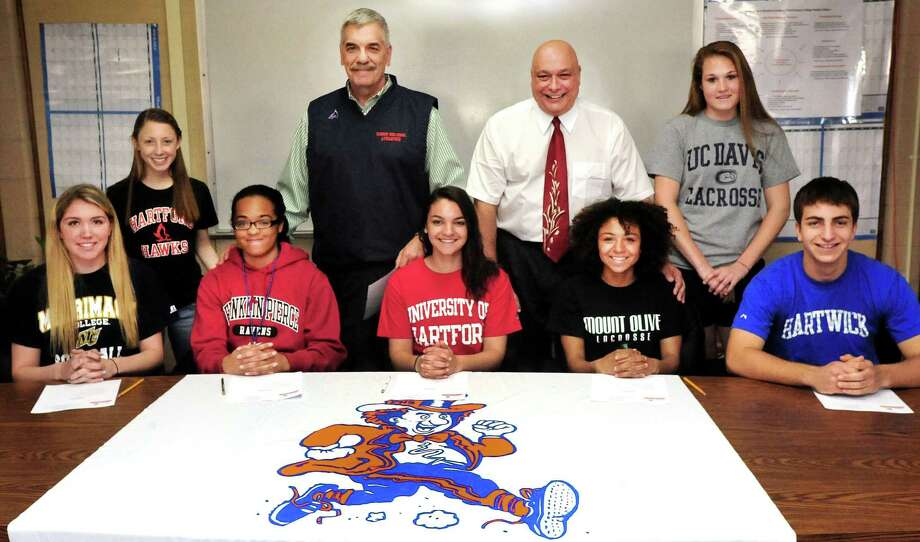 Student athletes and administrators pose for parents during the Danbury High School Athletic Department signing ceremony, in Danbury, Conn. Thursday, April 11, 2013. From left are Kara Orr, Kristen Dakin, Melanie Hill, athletic director Chip Salvestrini, Marisa Ferguson, school principal Gary Bocaccio, Raven Winters, Pauline Kaplan and Kenny Wilson. Photo: Michael Duffy / The News-Times