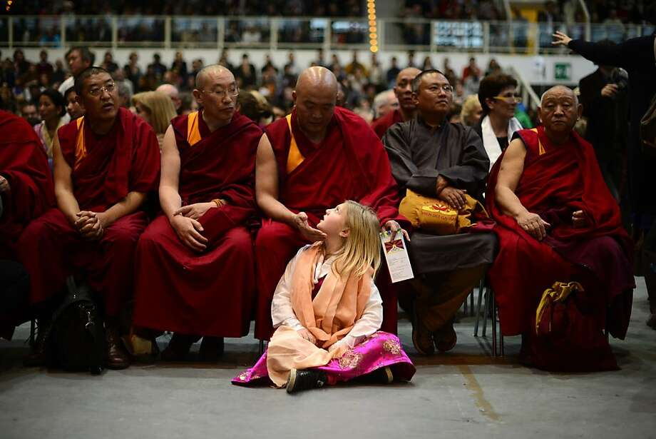 A monk gets a girl's attention during a public meeting of Dalai Lama, who was awarded the Award of Minorities by the Italian province of Bolzano, in Trento. Photo: Olivier Morin, AFP/Getty Images