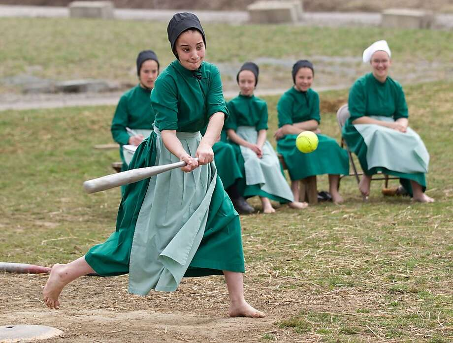 Plain ball! An Amish schoolgirl swings at a pitch during an after-class softball game in Bergholz, Ohio. She doesn't wear cleats, of course. They're so showy and prideful. Photo: Scott R. Galvin, Associated Press