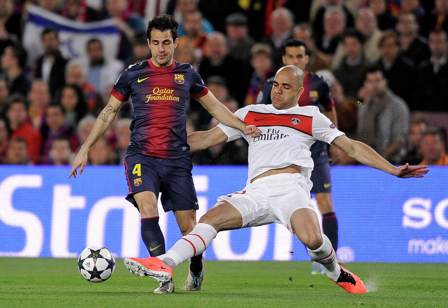 Barcelona's Cesc Fabregas, left, is challenged by PSG's Alex, from Brazil during the Champions League quarterfinal second leg soccer match between FC Barcelona and Paris Saint-Germain FC at the Camp Nou stadium in Barcelona, Spain, Wednesday, April 10, 2013. (AP Photo/Manu Fernandez) Photo: Manu Fernandez