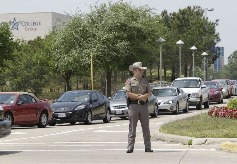 A law enforcement officer stands outside of Lone Star College where over a dozen people were injured in a stabbing incident, say officials. A suspect has been detained. Photo: Melissa Phillip