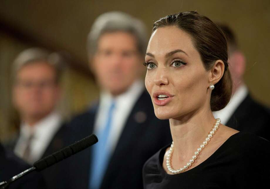 Flanked by G8 Foreign Ministers, US actress Angelina Jolie, in her role as UN envoy, talks during a news conference regarding sexual violence against women in conflict, during the G8 Foreign Ministers meeting in London, Thursday, April, 11, 2013. The ministers are meeting in London as Britain currently holds the G8 Presidency, with the heads of government G8 meeting set for June in Northern Ireland.(AP Photo/Alastair Grant, pool) Photo: Alastair Grant