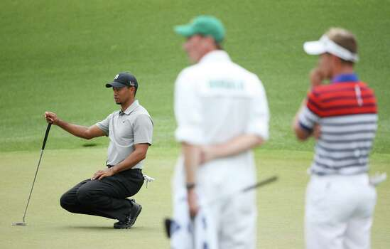AUGUSTA, GA - APRIL 11:  Tiger Woods of the United States lines up a putt on the the eighth green as Luke Donald of England looks on during the first round of the 2013 Masters Tournament at Augusta National Golf Club on April 11, 2013 in Augusta, Georgia. Photo: Andrew Redington, Getty Images / 2013 Getty Images