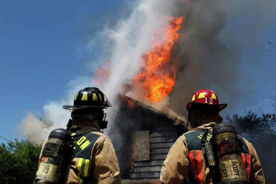 Firefighters watch a fire burn at 3300 Quitman. Photo: Johnny Hanson/Chronicle