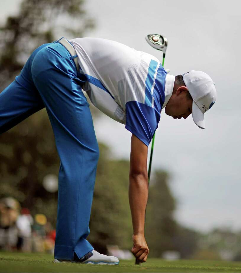 Amateur Guan Tianlang, of China, picks up his tee after hitting off the ninth hole during the first round of the Masters golf tournament Thursday, April 11, 2013, in Augusta, Ga. (AP Photo/David Goldman) Photo: David Goldman, Associated Press / AP