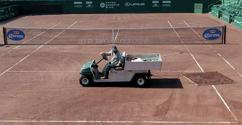 Grounds crew prepares center court for play  Thursday, April 11, 2013 after heavy rains over night at the U.S. Mens Clay Court Championships in Houston, Texas. Photo: Bob Levey, Houston Chronicle / ©2013 Bob Levey