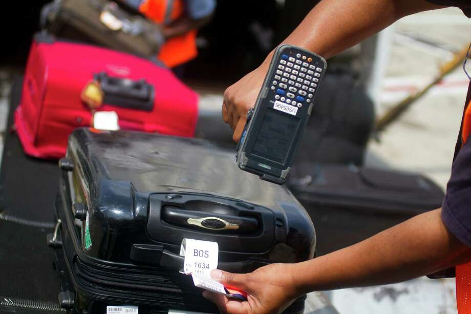 A worker scans luggage at Philadelphia International Airport, in Philadelphia, Aug. 3, 2012. Airlines and baggage system engineers are crediting technological advances with the lowest number of mishandled bags since 2005. (Jessica Kourkounis/The New York Times) Photo: JESSICA KOURKOUNIS / NYTNS