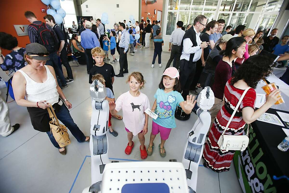 Alexandra Jurr, 8, left, and Kaitlyn Nguyen, 8, right, of Saratoga, high-five a PR-2 personal robot by Willow Garage during the Silicon Valley Robot Block Party 2013 in celebration of National Robotics Week at Stanford University's Automotive Innovation Facility in Stanford, Calif. on Wednesday, April 10, 2013.