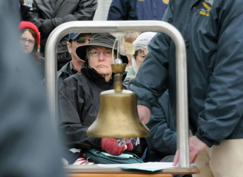 Sharon Wells of Bellingham, Wash., watches as veteran Tom Glenn rings a bell and James Irwin, commander of Albany-Saratoga Submarine Veterans, reads the names of the submariners who died at sea during a Tolling The Boats ceremony on Thursday, April 11, 2013 in Ballston Spa, N.Y. Sharon Wells is the daughter-in-law of George Wells, who was a commander in the Navy. Thursday marks the 113th anniversary of the United States submarine service. (Lori Van Buren / Times Union) Photo: Lori Van Buren
