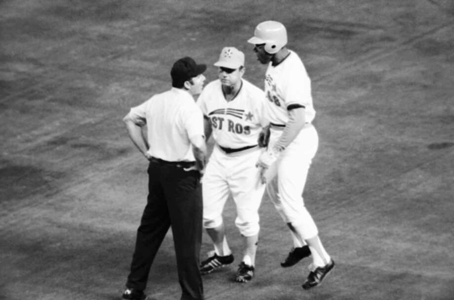 Houston Astros left fielder Bob Watson, right, hops up and down as he argues with first base umpire Dick Stello, left, over the call made on him in the third inning, April 20, 1974, Houston, Tex. Watson had grounded in the hole to short and the throw pulled the first baseman, Atlanta Ivan Murrell off the bag, but he made a tag at Watson which Stello ruled it was good for the out. First base coach Grady Hatton, center, stepped in between them and took over the argument. (AP Photo/Ed Kolenovsky) Photo: AP, STF / AP1974