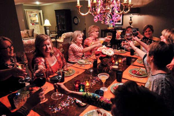 Members of a supper club that has been meeting since 1989 toast each other prior to beginning a Fiesta-themed meal at the home of Constance Kirk.