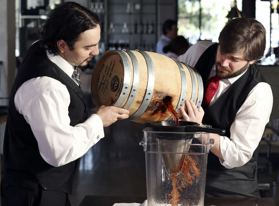 Arcade Midtown Kitchen bartender Matthew Sandoval (left) and bar manager Christopher Ware filter cocktail ingredients from a 5-gallon barrel for the Vieux Carre cocktail. Photo: Photos By Edward A. Ornelas / San Antonio Express-News