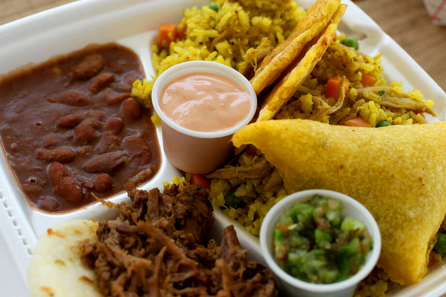 The Sabor Plate sampler from Sabor Colombiano offers  beans (upper left), arepa with carne (bottom left), an empanada (right), rice with chicken and tostones (fried plantains, nestled in rice). Photo: John Davenport / San Antonio Express-News