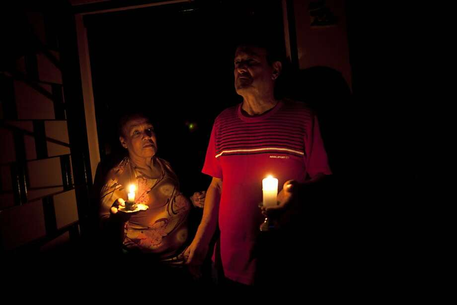 "In this April 8, 2013 photo, Pedro Martinez, 73, right, and his wife Aura, 60, hold lit candles during a power outage at their home in Valencia, Venezuela. ""This happens nearly every day,"" Martinez says of the blackout. It's was the day's second outage. The first struck just after noon. Outside Venezuela's capital, power outages, food shortages and unfinished projects abound; important factors heading into Sunday's election to replace Venezuela's late President Hugo Chavez, who died last month after a long battle with cancer. Polls show that support for acting President Nicolas Maduro, Chavez's hand-picked successor, may be eroding and constant power outages are a testament to the neglect many Venezuelans consider inexcusable in this major oil-producing state.  Photo: Ramon Espinosa, Associated Press"