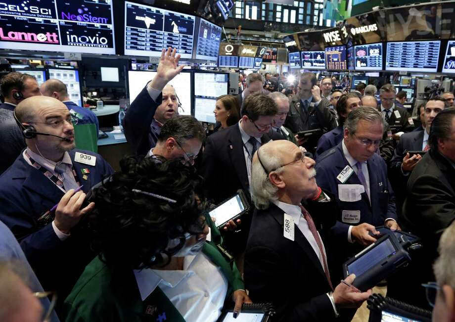 Traders gather at a post on the floor of the New York Stock Exchange Thursday, April 11, 2013.  Stock indexes are little changed in early trading on Wall Street after three days of gains. (AP Photo/Richard Drew) Photo: Richard Drew
