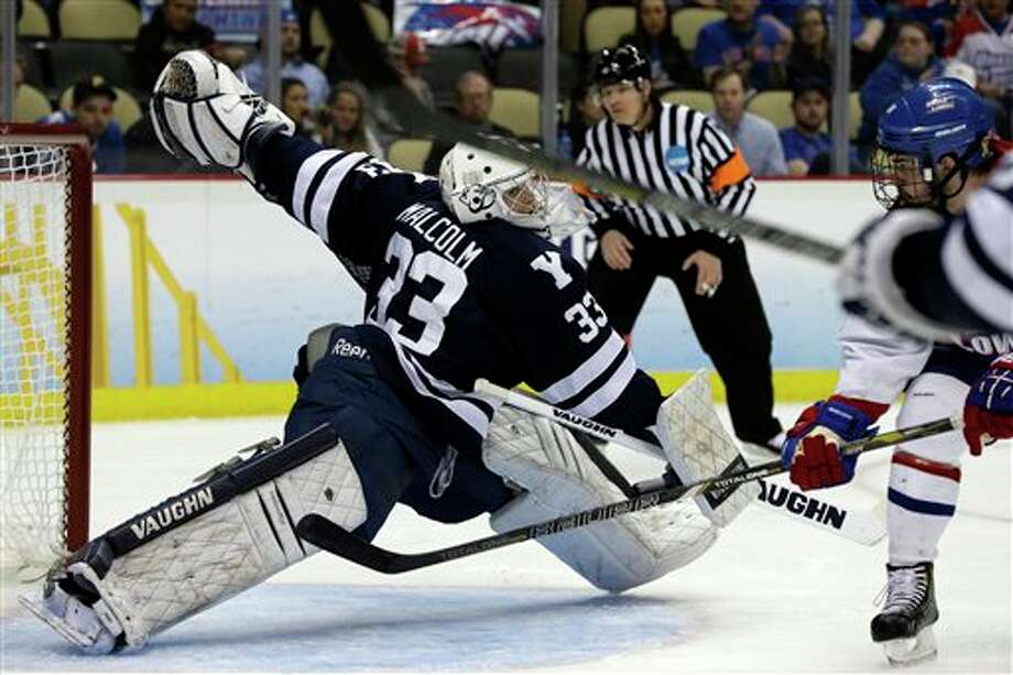 Yale goalie Jeff Malcolm (33) cannot stop a shot by UMass Lowell's Riley Wetmore, right, during the second period of an NCAA Frozen Four college hockey semifinal in Pittsburgh, Thursday, April 11, 2013. Photo: Gene Puskar, AP / AP