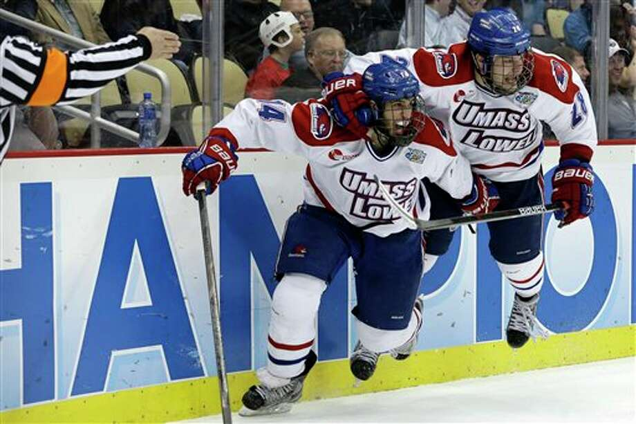 UMass Lowell center Joseph Pendenza (14) celebrates his second-period goal with  Jake Suter (28) during  an NCAA college hockey game against Yale in Pittsburgh Thursday, April 11, 2013. Photo: Gene Puskar, AP / AP
