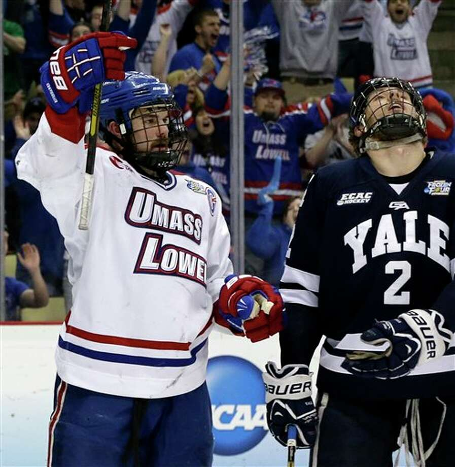 UMass Lowell captain Riley Wetmore, left, celebrates his goal during the second period as Yale defenseman Gus Young (2) skates back to his bench during an NCAA college hockey game in Pittsburgh Thursday, April 11, 2013. Photo: Gene Puskar, AP / AP