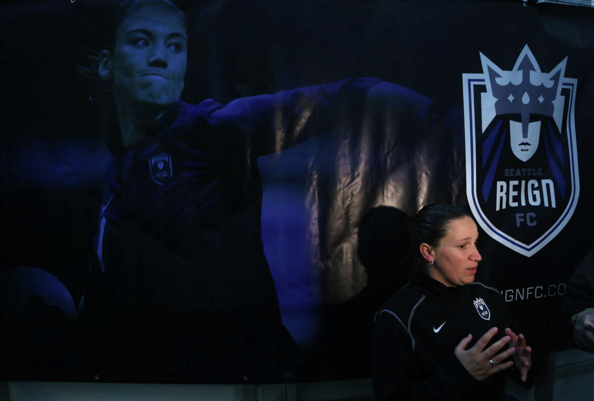 Seattle Reign head coach and general manager Laura Harvey speaks to media under a banner featuring injured player Hope Solo during practice at Starfire Sports in Tukwila. The new team kicks off their inaugural season with an away game against Chicago this weekend. Their first home game will be on May 4th at Starfire in Tukwila.