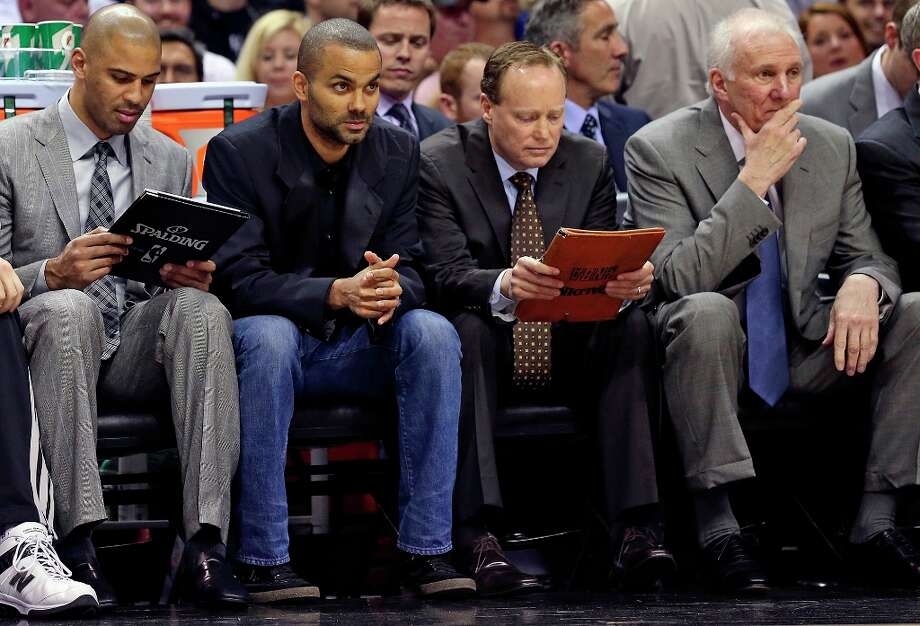 Tony Parker sits with Spurs coaches as they try to figure out a plan against the Trail Blazers at the AT&T Center on March 8, 2013. Photo: TOM REEL, San Antonio Express-News / San Antonio Express-News