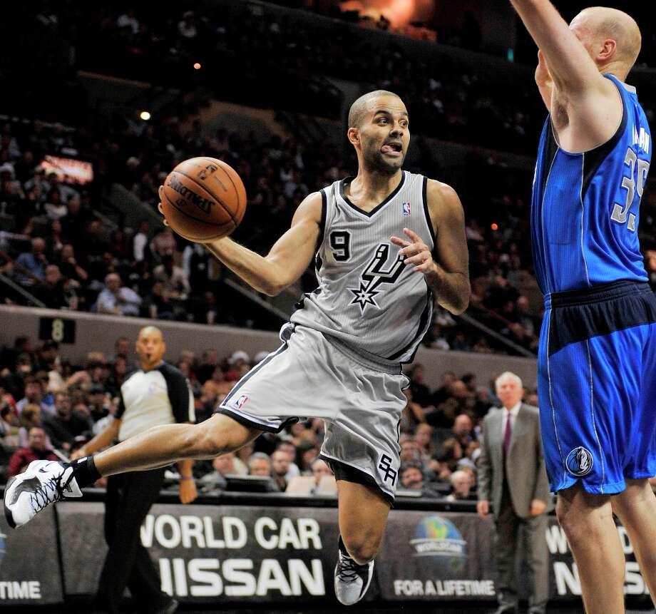 The Spurs' Tony Parker (left) passes around Dallas Mavericks' Chris Kaman during the first half Sunday, Dec. 23, 2012, in San Antonio. Photo: Darren Abate, Associated Press / FR115 AP