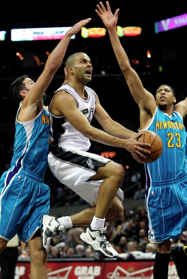 Spurs guard Tony Parker splits defenders in the lane in the thrid quarter as he leaves behind Greivis Vasquez (21) and Anthony Davis can't move in fast enough to help as San Antonio plays the New Orleans Hornets at the  AT&T Center on Dec. 21, 2012. Photo: Tom Reel, San Antonio Express-News / ©2012 San Antono Express-News