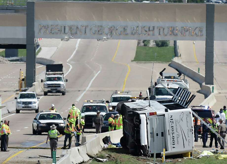 A charter bus rests on it's side after crashing on the President George Bush Turnpike Thursday, April 11, 2013, in Irving, Texas. The chartered bus overturned on the busy highway near Dallas killing at least two people and injuring several others, authorities said. (AP Photo/LM Otero) Photo: LM Otero