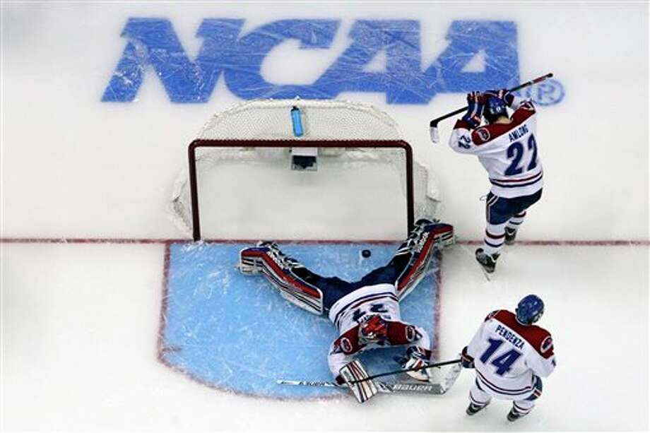 UMass Lowell goalie Connor Hellebuyck (37) lies in the crease as he reacts with defenseman Greg Amlong (22) and center Joseph Pendenza (14) to the winning goal by Yale's Andrew Miller during overtime of an NCAA Frozen Four college hockey semifinal in Pittsburgh, Thursday, April 11, 2013. Yale won 3-2. Photo: Gene Puskar, AP / AP