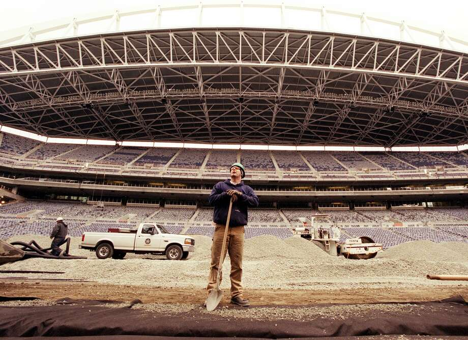 Gabriel Schoenfelder takes a break from shoveling gravel into an irrigation ditch in the  center of the new Seahawks Stadium on March 26, 2002, when construction was in its final stages. Photo: Joshua Trujillo, Seattlepi.com File