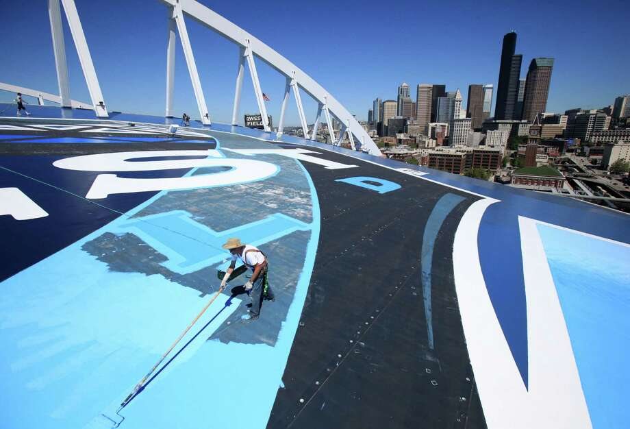 Bob Kehoe with TubeArt adds the finishing touches to a new paint job on the roof of Seattle's Qwest Field on July 15, 2010, About 1,000 gallons of paint were used to paint the roof and add the Qwest logo. Photo: Joshua Trujillo, Seattlepi.com / Seattlepi.com