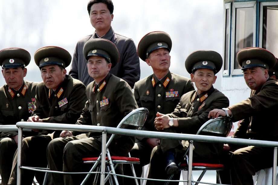 "In this Wednesday, April 10, 2013 photo, North Korean military officers look from a sight-seeing boat sailing on the Yalu River, the China-North Korea border river, near North Korea's town of Sinuiju, opposite to the Chinese border city of Dandong. North Korea delivered a fresh round of rhetoric Thursday with claims it had ""powerful striking means"" on standby for a missile launch, while Seoul and Washington speculated that the country is preparing to test a medium-range missile during upcoming national celebrations. (AP Photo) CHINA OUT"