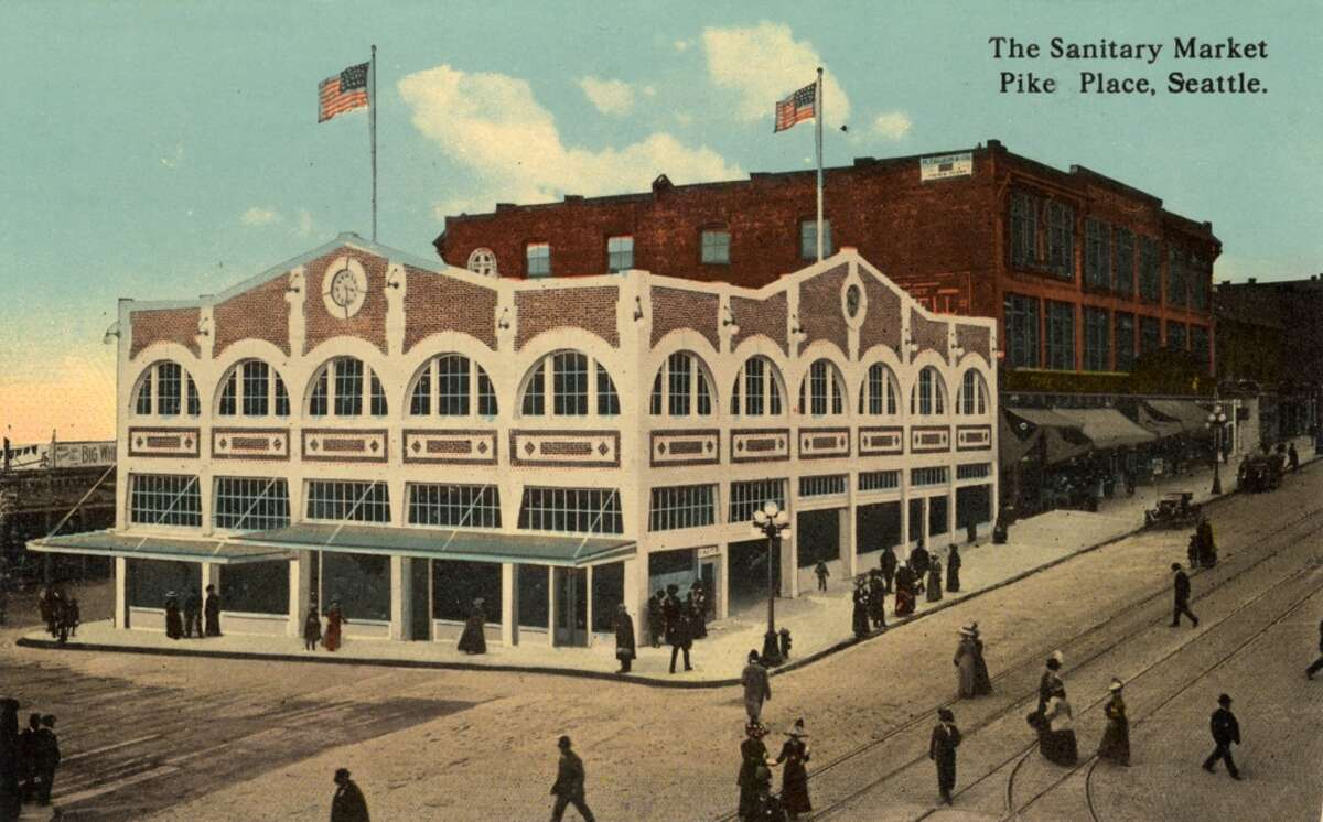 Vintage postcard circa 1911 showing the exterior of the Sanitary Market at Pike Place and the surrounding street.