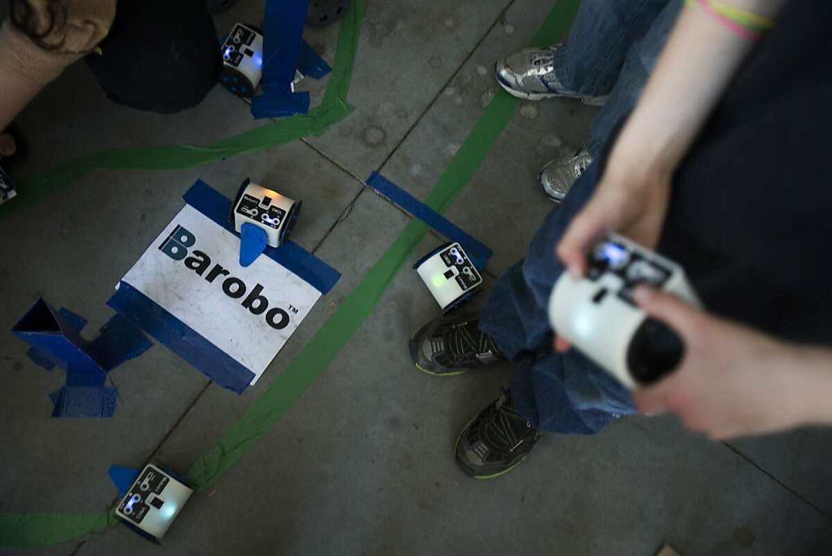 Attendees interact with modular robots by Barobo during Silicon Valley Robot Block Party 2013 in celebration of National Robotics Week at Automotive Innovation Facility in Stanford, Calif. on Wednesday, April 10, 2013.