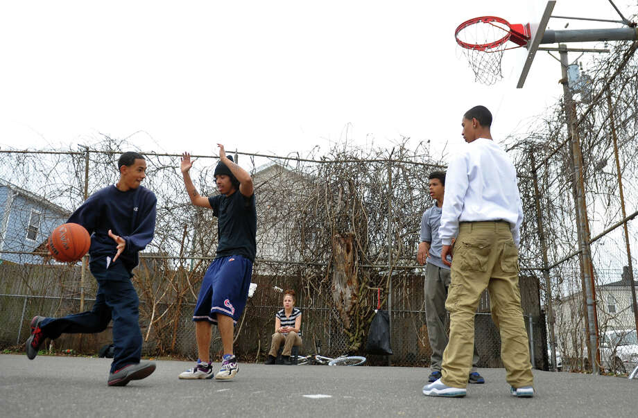 Jacob Ortiz, 15, left, drives to the basket as he plays with some of his friends at a court on Deacon Street in Bridgeport, Conn. on Thursday April 11, 2013. Photo: Christian Abraham / Connecticut Post