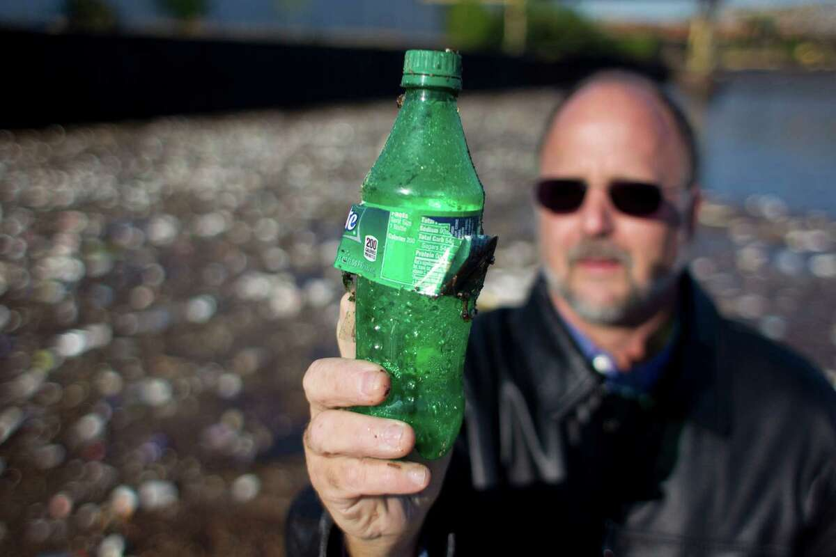 It's not hard for Robby Robinson of the Buffalo Bayou Partnership to find plastic bottles along the shoreline of Buffalo Bayou.
