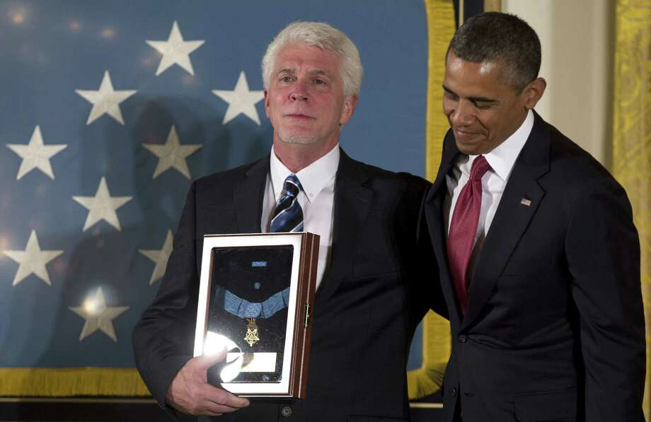 President Barack Obama stands with Ray Kapaun, nephew of Capt. Emil Kapaun, a Catholic priest and Army chaplain who died in 1951 at age 35 while he was a prisoner of war during the Korean War. Photo: Carolyn Kaster / Associated Press