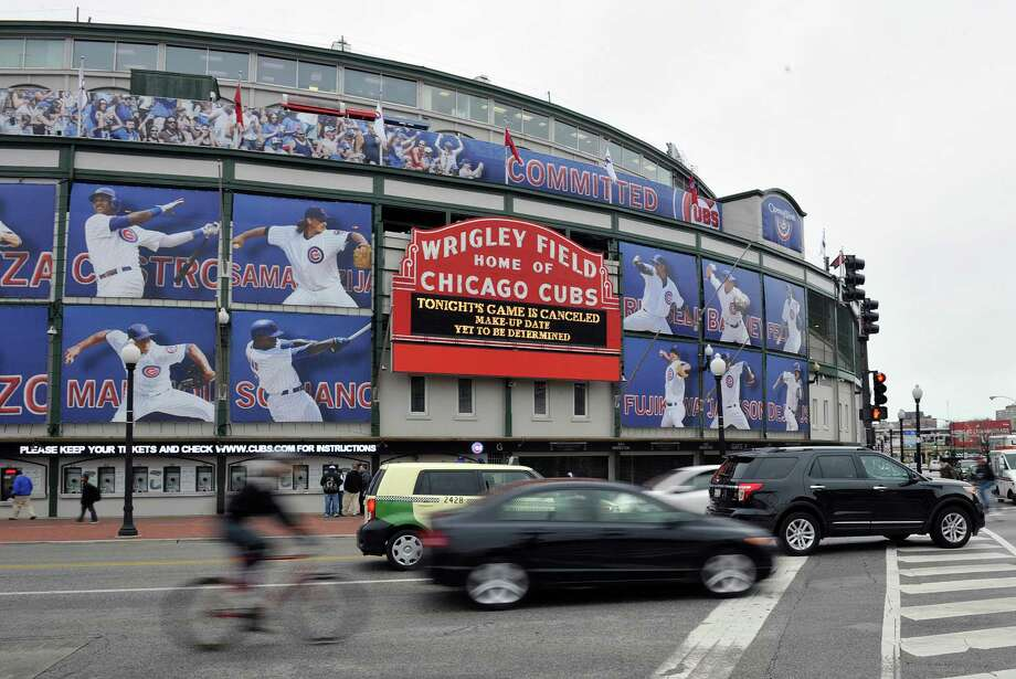 Traffic drives past Wrigley Field after the baseball game between the Milwaukee Brewers and Chicago Cubs was postponed due to inclement weather on Wednesday, April 10, 2013, in Chicago. (AP Photo/Jim Prisching) Photo: Jim Prisching / FR59933 AP