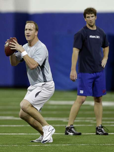 Peyton (front) and Eli Manning went back to school at Duke on Thursday. The brothers reunited with their college mentor, Blue Devils coach David Cutcliffe, to fine-tune their mechanics before voluntary NFL workouts begin next week. Photo: Gerry Broome / Associated Press