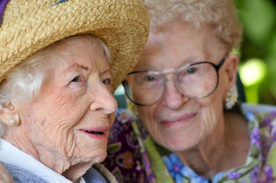 The sisters share a smile. Thuesen (left) remembers traveling by covered wagon at age 6 and drove a car till age 103. She even lived by herself until October.