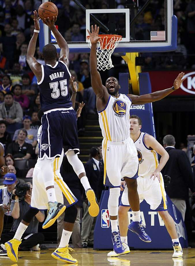 Festus Ezeli (right) contests Kevin Durant's shot; Durant had 31 points, 10 rebounds, eight assists. Photo: Carlos Avila Gonzalez, The Chronicle