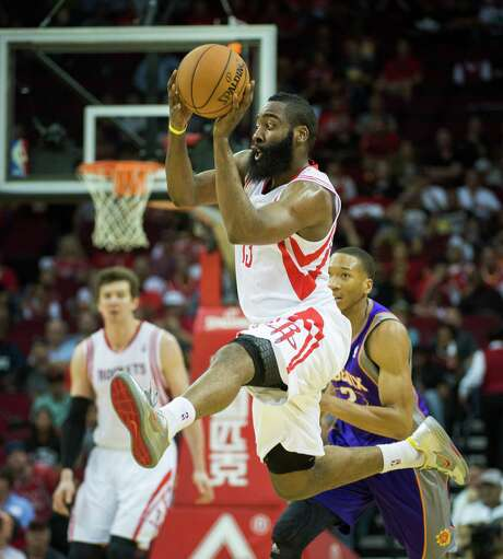 Houston Rockets shooting guard James Harden makes a pass after leaping for a loose ball against the Phoenix Suns during the first half of an NBA basketball game at Toyota Center on Tuesday, April 9, 2013, in Houston. ( Smiley N. Pool / Houston Chronicle ) Photo: Smiley N. Pool, Staff / © 2013  Houston Chronicle