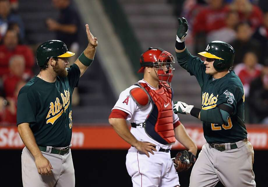 ANAHEIM, CA - APRIL 11:  Josh Donaldson (R) #20 of the Oakland Athletics is congratulated by Derek Norris (L) #36 after hitting a two-run home run, as catcher Chris Iannetta #17 of the Los Angeles Angels of Anaheim looks on in the sixth inning at Angel Stadium of Anaheim on April 11, 2013 in Anaheim, California.  (Photo by Jeff Gross/Getty Images) Photo: Jeff Gross, Getty Images