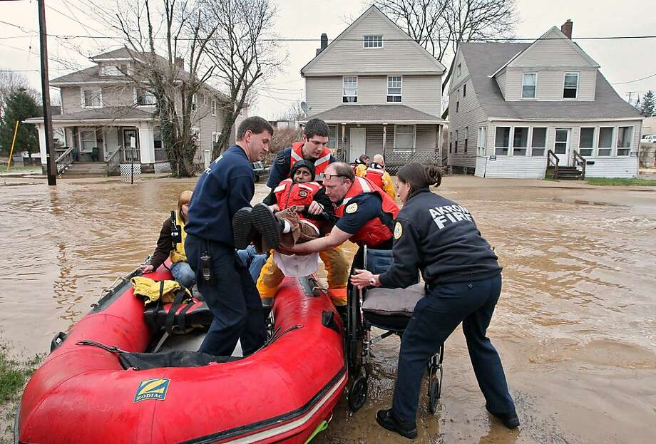 Yvonne Mayfield, 58, is lifted from a boat by Akron firefighters who rescued her from her North Valley Street home after a water main break flooded the area near North Street on Thursday, April 11, 2013 in Akron, Ohio.  Photo: Phil Masturzo, Associated Press