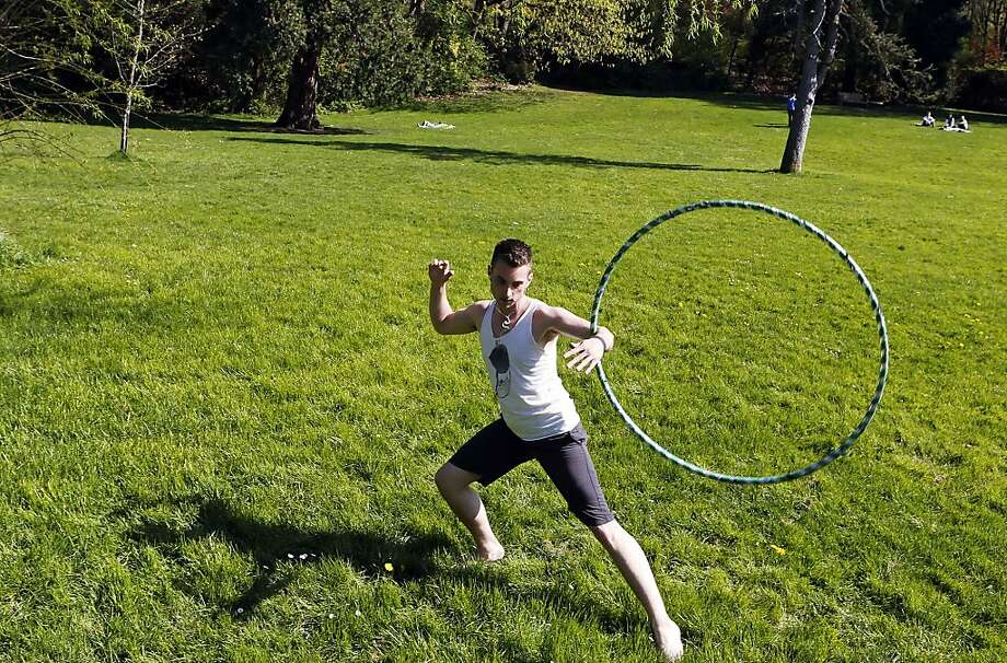 "University of Oregon senior Jesse Quinn takes advantage of the nice afternoon weather to practice a sport he calls ""hooping"" in Washburne Park in Eugene, Ore. on Thursday, April 11, 2013.  Photo: Chris Pietsch, Associated Press"