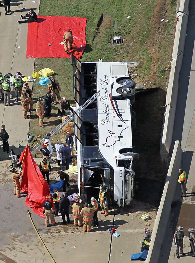 Rescue personnel work the scene of a Cardinal Coach Line charter bus accident on State Highway 161 in Irving, Texas on Thursday, April 11, 2013. Authorities say at least two people are dead and several injured after the chartered bus overturned.  Photo: Louis DeLuca, Associated Press