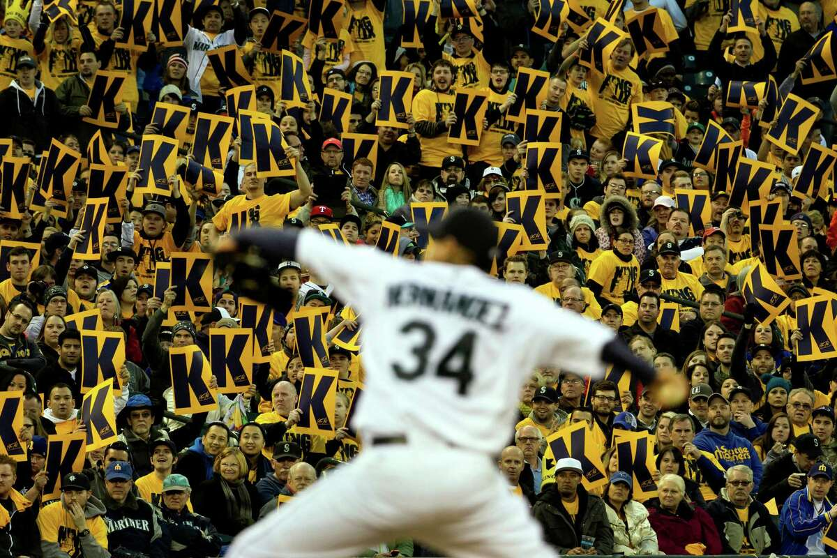 Backed by a sea of yellow King Felix signs, Mariners pitcher Felix Hernandez, center, pitches during a game against the Texas Rangers Thursday, April 11, 2013, at Safeco Field in Seattle. The Rangers beat the Mariners 4-3. The evening marked Felix Hernandez's opening game pitching at home for the 2013 season. The first 25,000 fans to arrive at Safeco Field were given discounted tickets and King Felix shirts.
